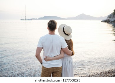 Back view of romantic couple at the beach and looking to the horizon.