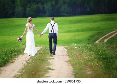 Back view of romantic couple of bride and groom walking hand in hand on rural road.