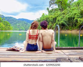 Back view of romantic young couple is sitting in swimsuit on wooden bridge enjoying beautiful mountains and river natural attractions in Dam at Khao Sok National Park, Surat Thani Province, Thailand.