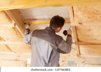 Back view of Roofer builder worker with ruler install plastic (mansard) or skylight window on attic with environmentally friendly and energy efficient thermal insulation rockwool