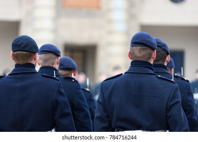 Back view of Royal Guards of the Swedish Royal Palace wearing navy blue uniforms with baret hats and rifles with bayonets performing the change of the guards at the Royal Palace, Stockholm, Sweden.