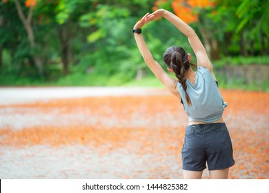 Back view of runner woman doing stretching and warming up her body before running. The benifit of stretching can increasing flexibility performance and reduce risk of injury.
