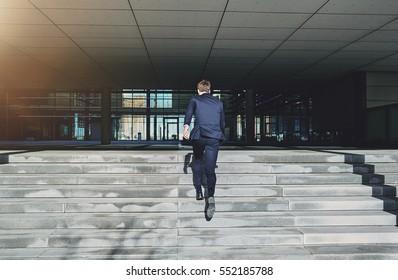 Back view of running to doors businessman. Horizontal outdoors shot