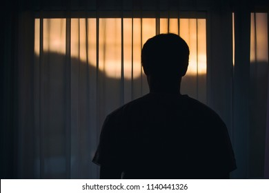 Back view of a sad man standing in front of the curtain and looking out the window.