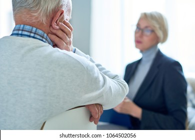 Back view  of sad senior man talking to female therapist during consultation, copy space