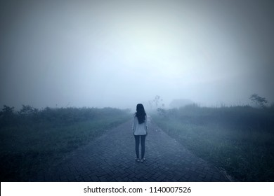 Back view of a sad woman standing alone in a misty morning. Shot in the mountain