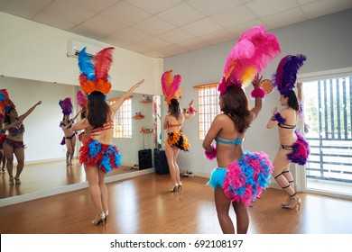 Back view of samba dancers wearing traditional colorful costumes sharpening their skills in spacious dance hall with full-wall mirrors
