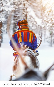Back view of Sami man at reindeer safari in a winter forest in Finnish Lapland