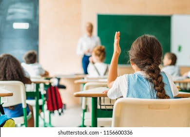back view of schoolgirl raising hand to answer teachers question during lesson
