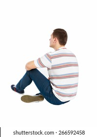 Back view of seated handsome man in t-shirt and jeans looking up. Rear view people collection. Backside view of person. Isolated over white background.