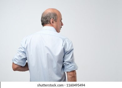 Back view of senior bald caucasiant man in casual shirt on gray background