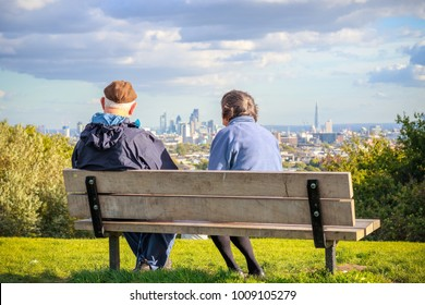 Back view of senior couple looking over London city skyline from Parliament Hill in Hampstead Heath