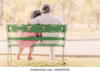 Back view senior couple sitting on the bench in the park enjoy a good time together