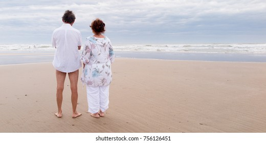 Back view of a senior couple standing on beach