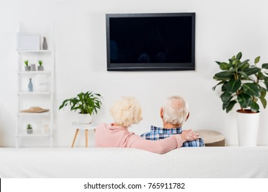 back view of senior couple watching tv and embracing on couch