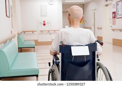 Back view of senior or elderly man sitting on wheelchair in hospital hallway