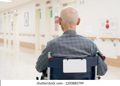 Back view of senior man in wheelchair at hospital hallway