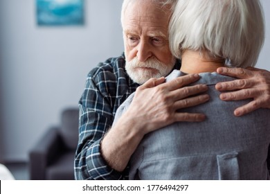back view of senior woman hugged by husband, sick on dementia