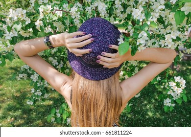 Back view of a sensual girl  holds on to her hat, dressed in a striped dress. Portrait of a beautiful woman on the background of the apple tree. Summer and spring trend in fashion.
