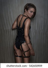 f8369fd5d4 Back view of sensual woman wearing black bodysuit with leather belts  looking at the camera over