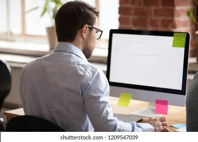 Back view of serious male employee work at computer writing business email to partner, focused man worker busy at pc, communicating with clients or customers online, consultant compose letter