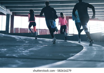 Back view of several people running over urban background. Copyspace