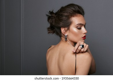 Back view of a sexy brunette woman in black dress, wears blue stone earrings and rings over grey dark background.