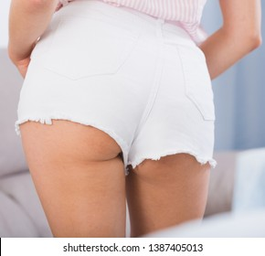 Back view of sexy girl body in white denim cut-offs shorts