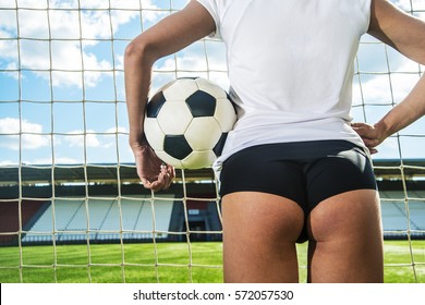 Back view. sexy Goalkeeper woman before a penalty kick. Empty stadium and blue sky with clouds on background. No face. Unrecognizable person. Space for inscription or objects. Big ass