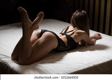 Back view of sexy model lying on bed in black panties