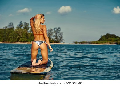 Back view of sexy woman with slender figure in bikini posing on surfboard in the sea
