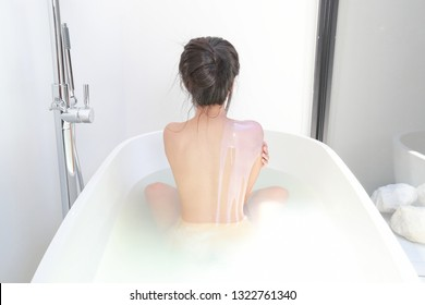 back view of sexy woman who is showering in bathtub and using body shower gel on her shoulder