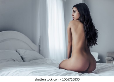 Back view of sexy young naked woman is sitting on white bed.