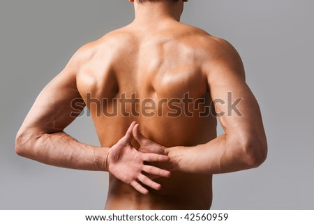 Back view of shirtless man keeping his hands behind back
