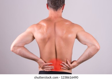 Back view of a shirtless man with lower back pain