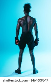back view of shirtless, muscular african american sportsman in boxing gloves on blue background