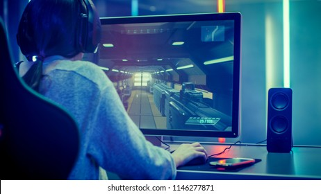 Back View Shot of the Beautiful Professional Gamer Girl Playing in  Online Video Game on Her Personal Computer. Casual Cute Geek Girl Wearing Headset. Dark Room Suddenly Lit by Neon Lights in Retro