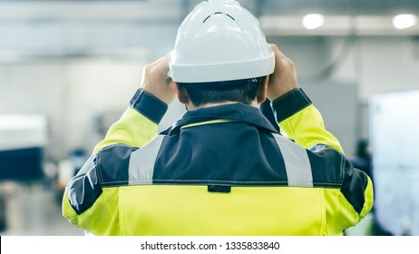 Back View Shot of the Industrial Engineer Wearing Protective Clothing Puts on Hard Hat and Walks Through Modern Manufacturing Facility with Automated Machinery Working in Background.