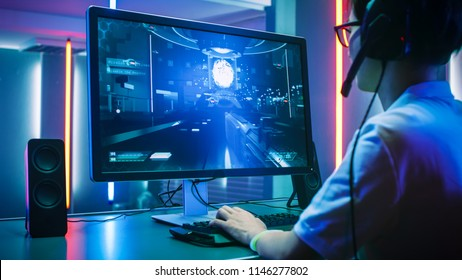Back View Shot of Professional Gamer Playing in First-Person Shooter Online Video Game on His Personal Computer. He's Talking with His Team Through Headset. Room Lit by Neon Lights in Retro Style.