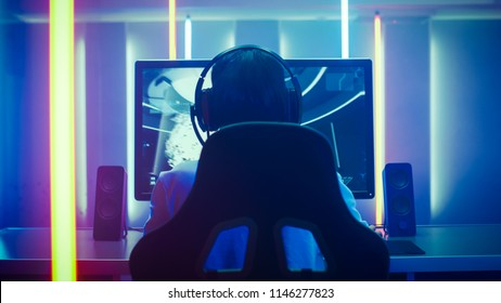 Back View Shot of the Professional Gamer Playing in First-Person Shooter Online Video Game on His Personal Computer. Room Lit by Neon Lights in Retro Arcade Style. Online Cyber e-Sport Internet.