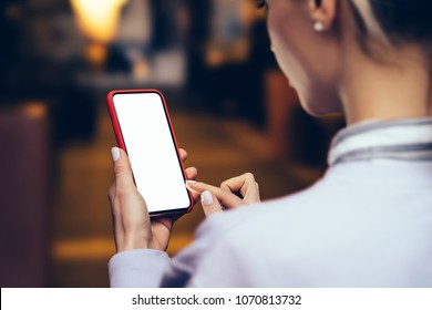 Back view from shoulder of female person looking to mock up copy space screen on mobile phone.Hipster girl using blank application on smartphone device.Close up view, texting message in social network