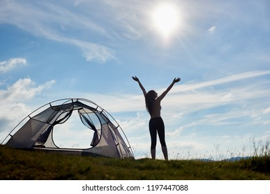 Back view of silhouette of attractive naked woman hiker standing near the tent with lifting hands up in the air, enjoying sunny day in the mountains. Camping lifestyle concept