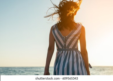 Back view silhouette of brunette beautiful woman walking along beach and sea sunset background. Cover idea. Female in dress walking on ocean, wind blowing hair. Loneliness and sadness concept.