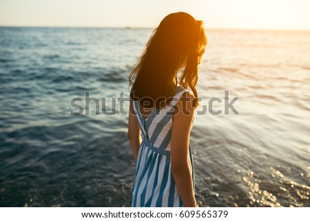 Back view silhouette of portrait brunette beautiful woman walking along beach and sea sunset background. Cover idea. Female in dress walking on ocean look to the sun. Loneliness and sadness concept.
