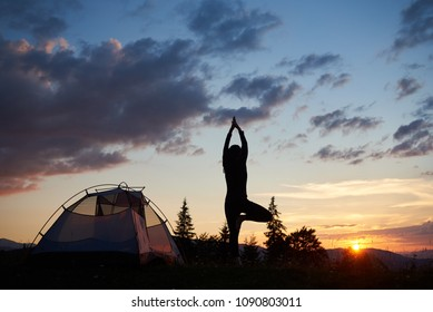Back view of silhouette young woman standing on leg in yoga tree pose on the top of hill near tent at daybreak under evening sky with perfect scenery fir trees, mountains and sunset