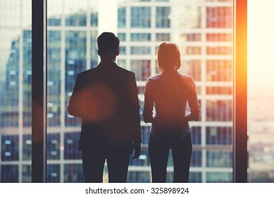 Back view silhouettes of two business partners looking thoughtfully out of a office window in situation of bankruptcy,team of businesspeople in fear or risk watching cityscape from skyscraper interior
