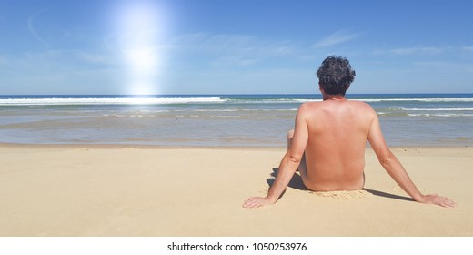 back view single man nudist on sea beach summer vacation
