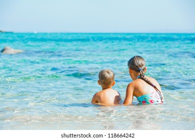 Back view of sister and brother playing and swimming in the transparent sea
