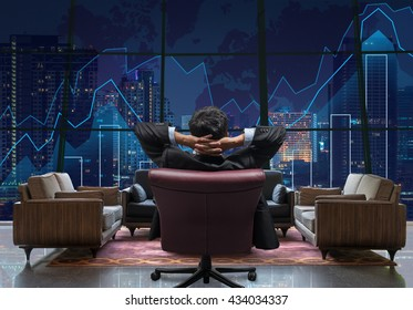 Back view of sitting businessman who is looking at Trading graph on the cityscape at night background,lobby sofa from dicut and retouch each elements, Business financial and investment concept