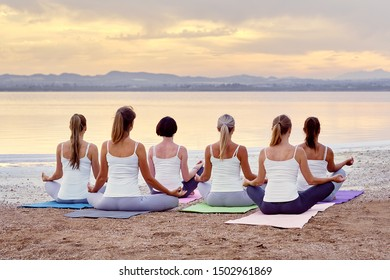 Back view six women group yogi female in activewear sitting in lotus position meditating do Siddhasana on sandy beach near sea feels placidity, stress relief balance harmony healthy lifestyle concept